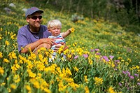 Father and son sitting in field of flowers in the Wasatch mountains near Alta in Utah USA