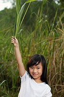Girl holding leaves in air