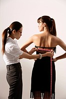 Chinese fashion designer measuring back of model´s dress