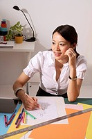 Chinese fashion designer smiling, sketching at work desk