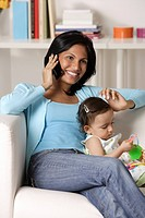 woman talking on mobile phone, sitting with baby