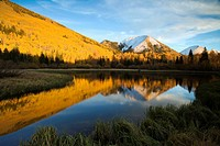 Wind rippled waters of Warner Lake reflect golden aspens and blue skies on an autumn afternoon in the La Sal mountains near Moab, Utah