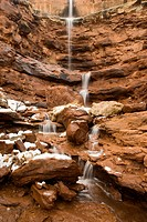 Snow melting high atop a sandstone wall sends a cascade of water down a narrow canyon in the Courthouse Towers area of Arches National Park, Utah, USA