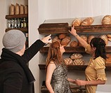 Man and woman pointing at bread on shelf
