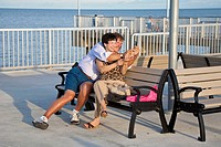 Man and woman couple take photos while sitting on bench on fishing pier at Cedar Key, Florida