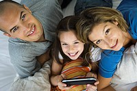 Girl lying between parents, playing handheld video game, all smiling up at camera
