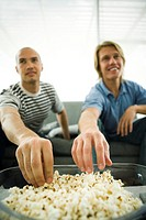 Two men sitting on sofa eating popcorn