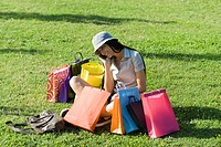 Young woman sitting in park, surrounded by shopping bags