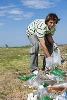 Young male picking up trash in field