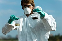 Person in protective suit holding flasks filled with polluted water