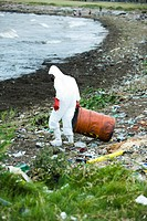 Person in protective suit removing hazardous waste from polluted landscape