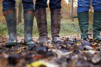 Three women in wellington boots in a forest