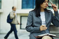 Businesswoman sitting on bench with agenda, putting on sunglasses