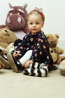 Little girl sitting with stuffed animals, portrait