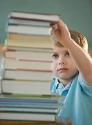 Boy taking book from stack