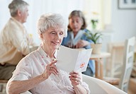 Senior woman reading greeting card