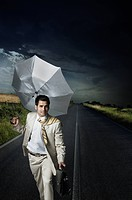 Businessman holding an umbrella and walking on the road