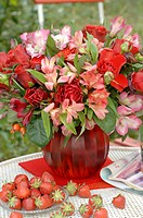 Layed table with bunch of flowers and strawberries