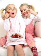 Two girls enjoying strawberries