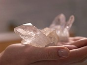 Helaing stone rose quartz on a opend hand