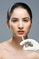 Surgeon´s hand injecting on woman´s lip