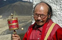 Old tibetan monk spinning a hand held prayer wheel Lama Yuru, Ladakh, India