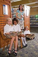 Portrait of elementary school teacher with pupils reading in library