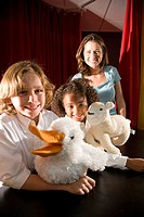 Portrait of elementary school teacher and pupils in puppet theatre