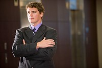 Portrait of young businessman standing in lobby, arms folded