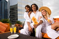 Portrait of group of young adults relaxing on rooftop terrace in city