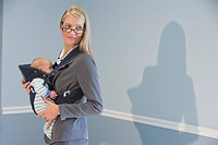 Portrait of young businesswoman holding baby at work