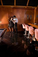 Portrait of African American man talking to woman in flapper dress in 1920s billiards bar
