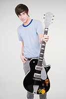 Portrait of a teenage boy holding a guitar