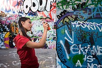 A young woman spraying graffiti