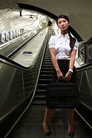 A businesswoman holding a briefcase on an escalator
