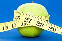 A tape measure wrapped around an apple