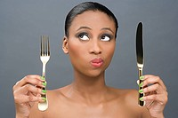 Woman holding a knife and fork (thumbnail)