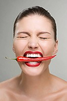 Woman biting a red chili pepper