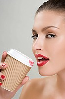 Woman drinking coffee from a paper cup