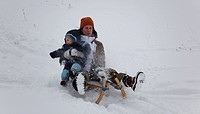 mother with child tobogganing
