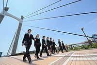 Group Of Businesspeople Walking On Bridge