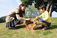 Japanese woman and boy playing in park with dogs