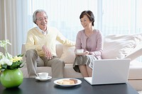 Senior couple having coffee on couch in living room