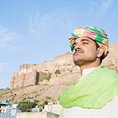 Man with fort in the background, Meherangarh Fort, Jodhpur, Rajasthan, India