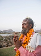 Sadhu standing in a prayer position, Hampi, Karnataka, India