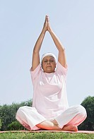 Woman practicing yoga in a park, New Delhi, India