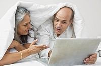 Couple using a laptop on the bed and smiling