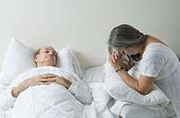 Ill man lying on the bed with his worried wife sitting beside him