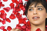 Close_up of a woman lying with rose petals