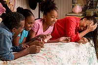 African family playing cards on bed
